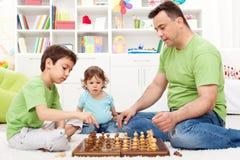 Menino da criança que olha o jogo de xadrez Fotografia de Stock Royalty Free