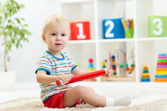 Menino da criança que senta-se com o lápis vermelho grande Imagens de Stock Royalty Free