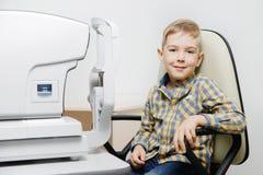 Menino da criança que sorri na clínica do oftalmologista da cadeira fotos de stock