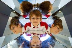 Menino da criança que tem o divertimento com experiências com espelhos em um musem Retrato do aluno de sorriso feliz Imagens de Stock