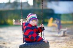 Menino da criança que tem o divertimento no balanço chain fora Imagem de Stock