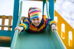 Menino da criança que tem o divertimento no balanço chain fora Fotos de Stock Royalty Free