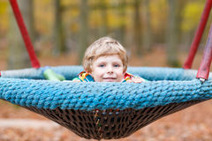 Menino da criança que tem o divertimento no campo de jogos do outono Imagens de Stock Royalty Free