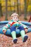 Menino da criança que tem o divertimento no campo de jogos do outono Fotos de Stock Royalty Free