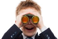 Menino da criança no terno de negócio que guarda a lente dos binóculos que procura d Imagem de Stock