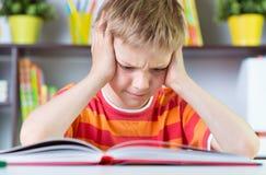 Menino da escola primária no boock da leitura da mesa imagens de stock