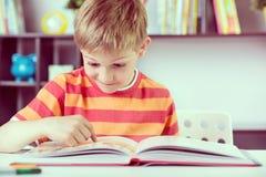 Menino da escola primária no boock da leitura da mesa fotos de stock