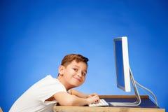 Menino da idade escolar que senta-se na frente do portátil do monitor no estúdio Imagem de Stock