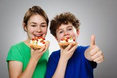 Menino da menina que come o waffle Imagem de Stock
