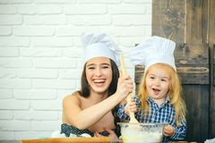 Menino da mulher e da crian?a que sorri em chap?us do cozinheiro chefe com colher imagens de stock royalty free