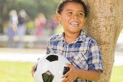 Menino da raça misturada que guardara a bola de futebol no parque Fotografia de Stock Royalty Free