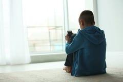 Menino da virada com o smartphone que senta-se perto da janela dentro foto de stock royalty free