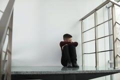 Menino da virada que senta-se na escadaria dentro fotografia de stock