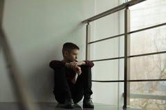 Menino da virada que senta-se na escadaria dentro espa?o foto de stock