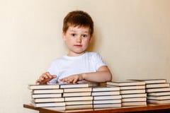 Menino de 6 anos bonito que senta-se em uma mesa com as pilhas de livros imagens de stock royalty free