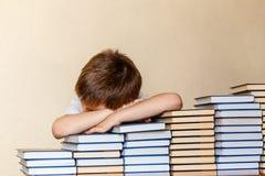 Menino de 6 anos que senta-se na tabela, em suas mãos e em cabeça no livro imagem de stock