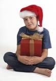 Menino de assento com presente do Natal fotografia de stock royalty free