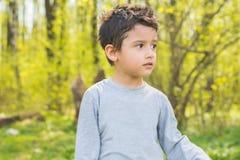 Menino de cabelo escuro em uma floresta Fotos de Stock Royalty Free