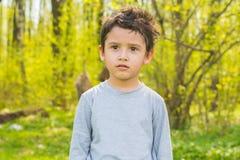 Menino de cabelo escuro em uma floresta Fotografia de Stock Royalty Free