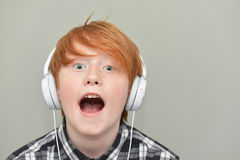 Menino de cabelo vermelho engraçado com fones de ouvido Imagem de Stock Royalty Free