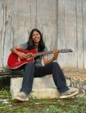 Menino de cabelos compridos asiático que joga a guitarra Fotos de Stock Royalty Free