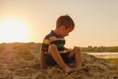 Menino de cinco anos bronzeado que joga na areia na praia, verão Fotografia de Stock Royalty Free