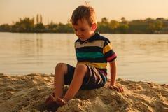 Menino de cinco anos bronzeado que joga na areia na praia, verão Fotografia de Stock