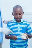 Menino de ensino do dentista como escovar os dentes imagens de stock