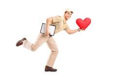 Menino de entrega que entrega o objeto dado forma coração Imagem de Stock Royalty Free