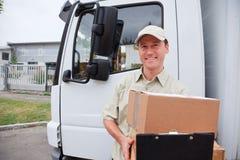 Menino de entrega que está ao lado de um caminhão foto de stock royalty free