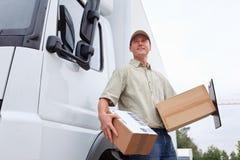 Menino de entrega que está ao lado de um caminhão imagens de stock