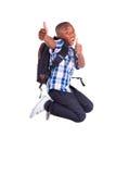 Menino de escola afro-americano que salta e que faz o preto dos polegares acima - Fotografia de Stock Royalty Free