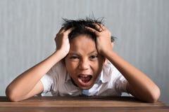 Menino de escola asiático que guarda sua cabeça na tabela de madeira que sente assim o esforço foto de stock
