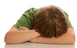 Menino de escola com cabeça na mesa Imagem de Stock