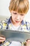 Menino de escola com tabuleta eletrônica imagem de stock