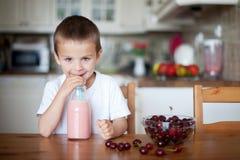 Menino de escola feliz que bebe um batido saudável como um petisco Imagens de Stock Royalty Free