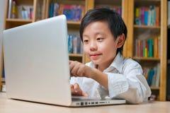 Menino de escola na camisa branca na frente do computador portátil Fotografia de Stock