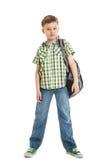 menino de escola nas calças de brim com uma trouxa isolada fotografia de stock royalty free