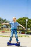 Menino de escola no hoverboard azul Foto de Stock Royalty Free