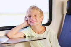Menino de escola novo no trem com telefone celular Foto de Stock Royalty Free