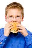 Menino de escola novo que come o Hamburger imagem de stock