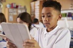 Menino de escola primária da raça misturada que usa o tablet pc na classe Imagens de Stock Royalty Free