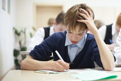 Menino de escola que esforça-se para terminar o teste na classe. Imagens de Stock Royalty Free