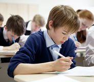 Menino de escola que esforça-se para terminar o teste na classe. Fotos de Stock