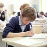 Menino de escola que esforça-se para terminar o teste na classe. Fotografia de Stock