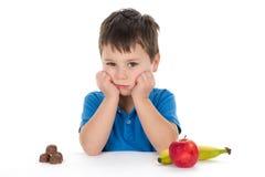 Menino de escola que senta-se na frente de um chocolate e dos frutos Imagens de Stock