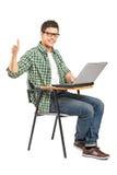 Menino de escola que trabalha em um portátil e que dá o polegar acima Foto de Stock