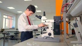 Menino de escola secundária no microscópio em um laboratório da escola, fazendo a pesquisa da biologia vídeos de arquivo