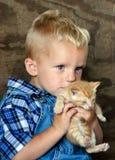 Menino de exploração agrícola que guarda um gatinho Foto de Stock Royalty Free