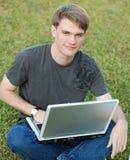Menino de faculdade em um portátil Fotografia de Stock Royalty Free